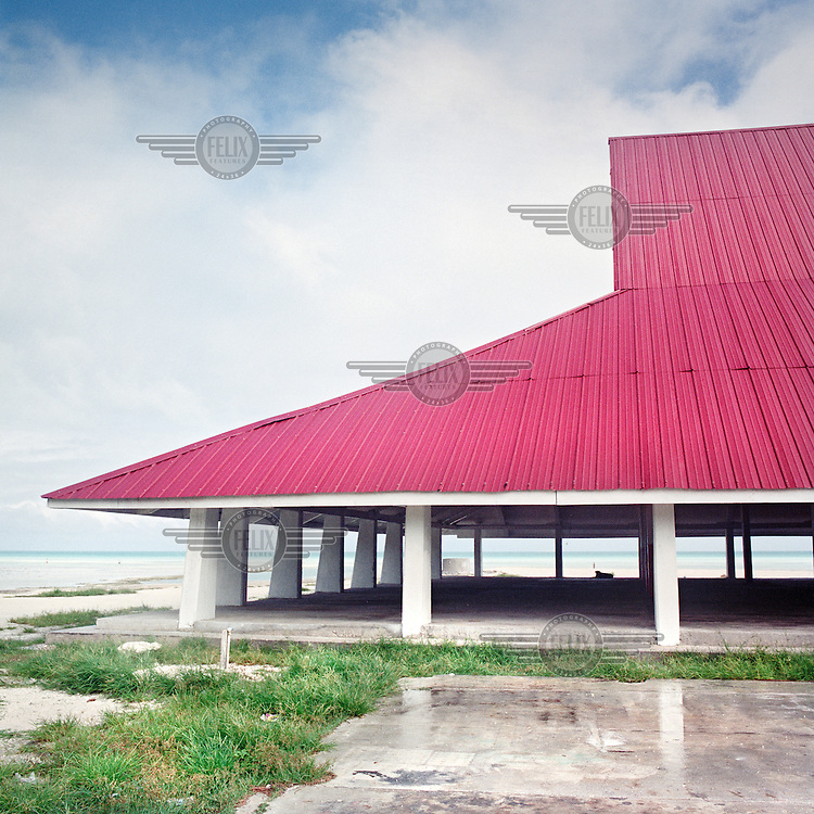 A large maneaba, community hall, on the edge of the lagoon has recently exchanged the thatched pandanus roof for steel. The modern material will withstand extreme weather conditions occuring more readily in the face of global climate change.