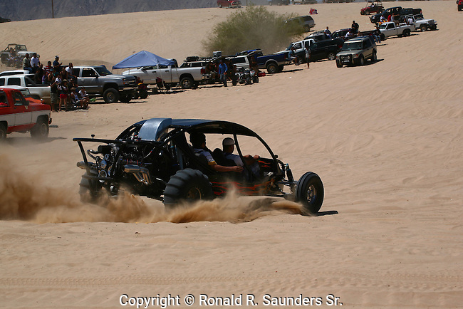 TRUCKS LINE the SAND DUNES WHILE<br /> ALL TERRAIN VEHICLE DRIVES THROUGH the SAND DUNES