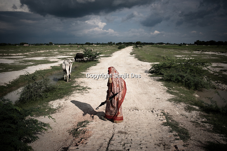 A woman walks past the dried up parched farm lands in Akhori village in Unnao in Rae Bareli, Uttar Pradesh, India. The 4 month annual rainfall is crucial to summer sown crops as 60% of the farmlands are rainfed. North India experienced scanty rainfall in late june to july. Till August, rain in India has been 26% below 5 year average. Late rains moist the fields but it is not enough for rice, sugarcane, oilseeds and pulses. Late rains also damage the alternate crops that need less water.