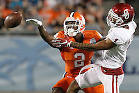 Clemson cornerback Mackensie Alexander (2) breaks up a pass intended for Oklahoma wide receiver K.J. Young (1) in the third quarter at the Russell Athletic Bowl in Orlando, Fla., on Monday.