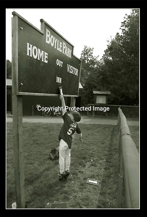 A little leaguer needs some extra inches to keep the score up during a Little League game in Mill Valley, California.