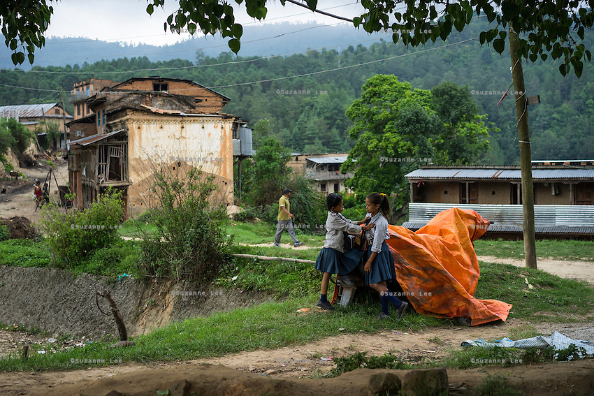 Binita Tamang (10, left) plays with her school friend as Binita's partially-collapsed house is seen in the background in Kavre, Bagmati, Nepal on 30 June 2015.  Binita was nearly trapped on the 2nd floor of the building when the earthquake struck, only managing to get outside after the shaking stopped. Her mother, Kalpana, a widow with 3 children, has been supported by SOS Children's Villages for many years now and had receive the Home-in-a-Box after the earthquake destroyed her house, almost killing her two daughters. She now lives in a temporary shelter, sharing her dwelling with farm animals, and is trying to make ends meet by weaving bamboo baskets to supplement the financial assistance provided by SOS Childrens Villages. The NGO mostly supports her children's welfare and schooling as well as provides her with essential household and schooling items like kitchen utensils and school books and uniforms. Photo by Suzanne Lee for SOS Children's Villages