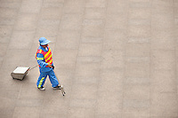 Daytime landscape view of a Sanitation Worker Walking Near The Lu Jia Zui Metro Station in Pudong.  © LAN
