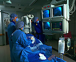 surgeons watching monitors in operating room while performing cardiac catheterization
