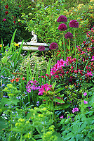 Birdbath with figurine set amid lush Spring garden of allium, azaleas, geranium, California poppy, and perennials, Vancouver, BC.