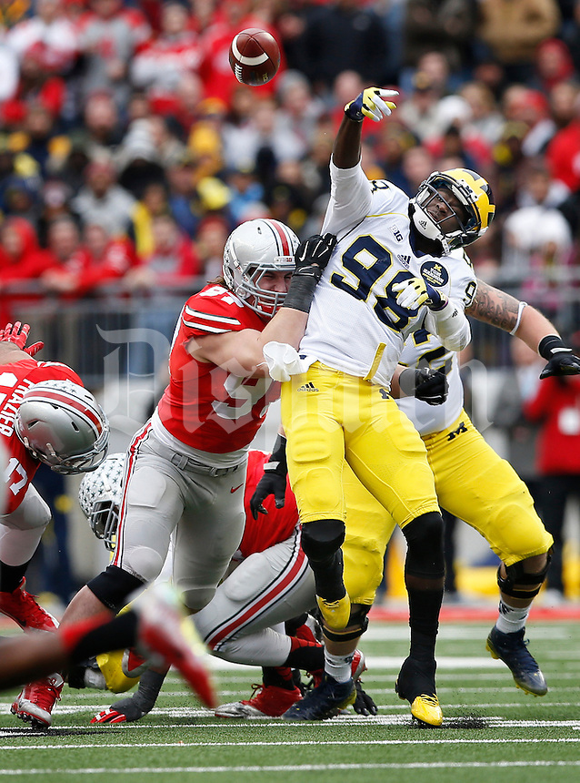 Ohio State Buckeyes defensive lineman Joey Bosa (97) forces Michigan Wolverines quarterback Devin Gardner (98) to throw an incomplete pass during the second quarter of the NCAA football game at Ohio Stadium on Nov. 29, 2014. The Buckeyes won 42-28. (Adam Cairns / The Columbus Dispatch)