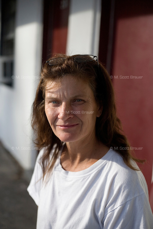 """Sheila Esposito, 50, of Wilmington, Mass., will be staying at Motel Caswell for a week, photographed at the motel in Tewksbury, Massachusetts, USA, on Tuesday, Oct. 11, 2011. Esposito says she has known the motel since she was a child, and has been living at the motel periodically over the past few years, always in  room 231 at the end of the motel's second building. She's staying at the motel with her dog Alex.  She says the motel is a place to stay """"just for the time being."""" She's an LNA (licensed nurse assistant) and is looking for work in the field. On this day, she was offered 3 jobs, though none in healthcare.  With her husband, she bought a house about 10 years ago, but lost it 5 years ago.  To move into an apartment in the area, she estimates that she'd need about six thousand dollars to cover first and last month's rent, security deposit, and a pet deposit. Paying $800/month, Esposito says, """"How can you beat that? You could go down the road and pay $200 a night and they wouldn't let the dog in."""" ..The motel is owned by Russell Caswell. Caswell's father built the motel in the 1950s. Now, conservative activitists are trying to use federal asset-forfeiture laws to seize the motel, saying that the motel is used by drug dealers to conduct business.  The legal challenge intends to show evidence tying the property to crimes in order to seize the motel.....CREDIT: M. Scott Brauer for the Wall Street Journal.slug: FORFEIT"""