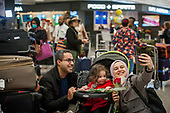 A family is united and takes a selfie, as passengers arrive from Dubai after a 14-hour flight on Emirates flight 231, at the international terminal at Dulles International Airport in Dulles, Va., Monday, March16, 2020. Some people are taking the precaution of wearing face masks as they arrive to be greeted by family and or friends. Credit: Rod Lamkey / CNP