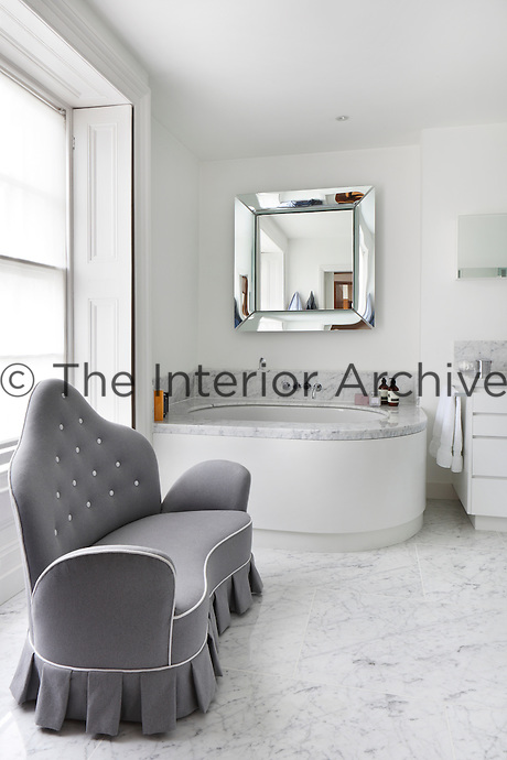 A spacious white bathroom with a shining grey and white marble floor. The vintage mirror is by Philippe Stark and the sofa by Vincenzo Caffarella