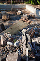 A close up of residential home demolition debris containing scraps of brick, concrete, wood, gypsum wallboard, plaster, metal, dirt, and fine dust particles.
