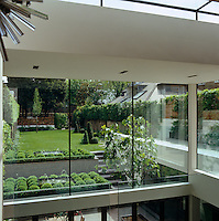 View through the glass walls of the extension from the living room to the landscaped garden