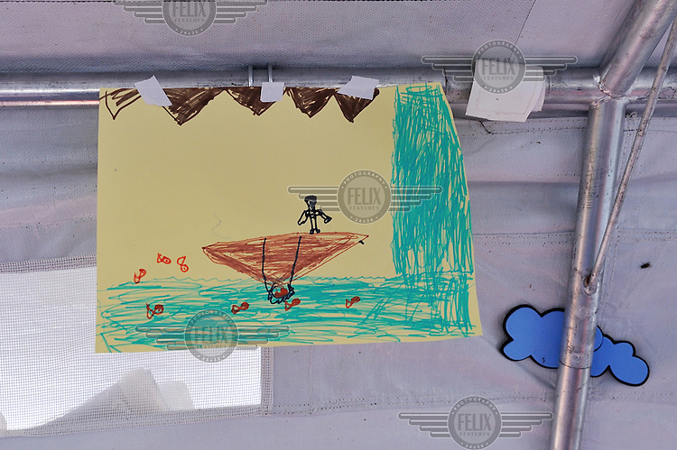 A child's drawing hangs in a play area for children at Vinojug reception centre. The center is a kilometer inside the Republic of Macedonia from the Greek border and most refugees and migrants arrive less then 24 hours after leaving the Greek Islands, to which they crossed from Turkey on small boats such as the one pictured. /Felix Features