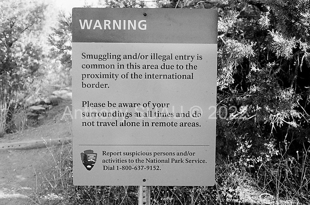 Coronado National Forest, Arizona<br /> May 4, 2008<br /> <br /> At a mountain peak in Coronado National Forest a sign for tourists to watch out for illegal immigrants marks the spot.<br /> <br /> The vast majority of the Arizona/Mexican border is now marked by vehicle barrier or high fencing. Also a graded road runs along the majority of this new fencing.