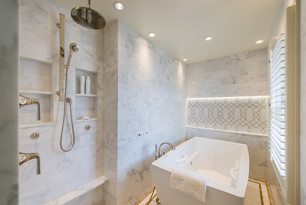 Luc, a hand-cut mosaic shown in polished Afyon White and  Sylvia Gold, is part of the Aurora® collection by New Ravenna. Master Bath Design by Meghan Browne