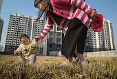 A former farmer plays with her granddaughter in a &quot;replacement housing block&quot; in Hebei province, just outside Beijing, built for people like her who has lost their farmland to a new phase of state-driven urbanisation. Because of the speed of the construction roll-out across China, they follow mostly the same blueprint. <br /> <br /> For generations, Chinese farmers picked vegetables on family plots in China, a mainly agrarian society right up until the 20th century.<br /> <br />  <br /> <br /> Faced with slowing exports, Communist leaders are pushing ahead with a historic plan to move 100 million rural residents into towns and cities by 2020 to create a new middle class and boost demand.<br /> <br />  <br /> <br /> As a non-resident Chinese, Justin views the situation both as a concerned citizen and a questioning outsider. As he crisscrosses the country talking with farmers, he gets a feeling the government&rsquo;s maths might be right, but wonders at the long-term consequences for society.<br /> <br />  <br /> <br /> What happens to humanity -- and the earth -- when millions of subsistence farmers clamor to join the consumptive middle class in half a decade?<br /> <br />  <br /> <br /> This series for Sony is shot in Hebei province, just outside Beijing, as part of his bigger project.