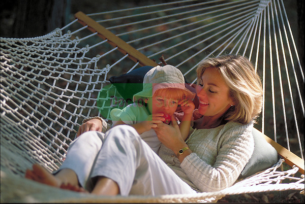 laughing mother and young child lying in hammock