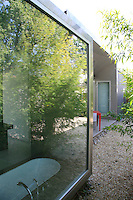 The frame of the house has been constructed from stainless steel; seen here a bay window in which a bath has been located
