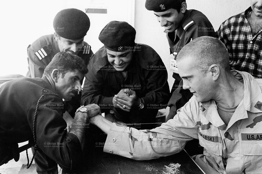 Iraq. Kirkuk. An american soldier from the coalition force plays an arm-wrestling match against a kurd soldier from the peshmerga forces. The kurdish man wins the fight. © 2003 Didier Ruef