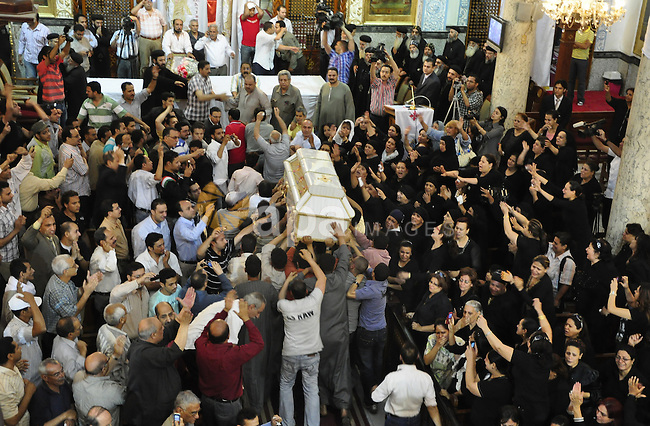 """Egyptian Coptic Christians carry the coffin of a victim of sectarian clashes during a funeral in Cairo on May 8, 2011 as Egypt's military rulers warned they will use an """"iron hand"""" to protect national security after clashes between Muslims and Christians in the Egyptian capital killed 12 people and injured scores.  Photo by Ahmed Asad"""