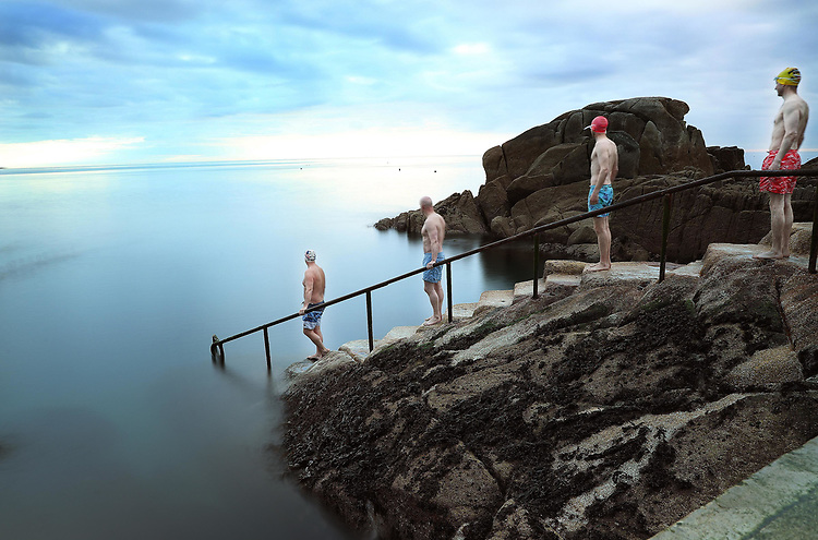"""No Repro Fee.<br />Distance Dipping…<br />Swimmers ready to take their daily dip line up respecting the advised Irish social distancing at one of Dublin's iconic bathing areas """"The Forty Foot"""" in Sandycove, Co. Dublin. <br />Pic. Robbie Reynolds"""