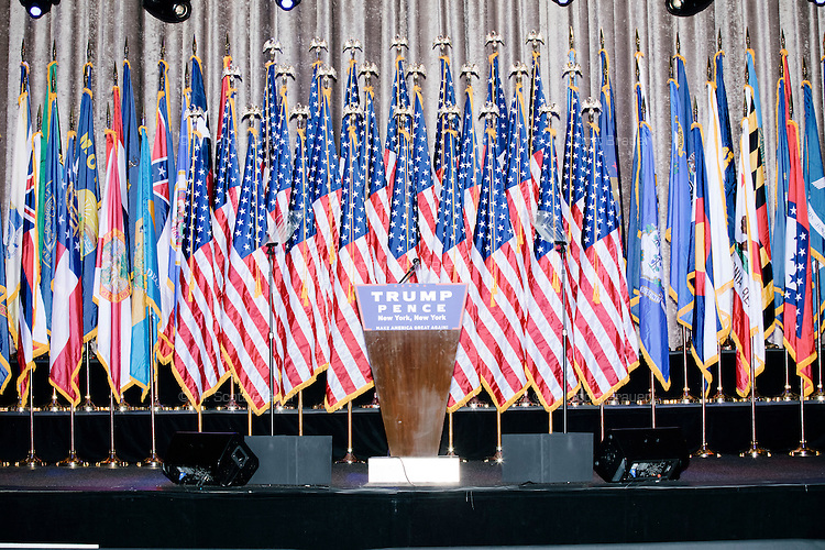 Flags stand behind a Trump/Pence podium in the ballroom at the Midtown Hilton Hotel in New York, New York, on the morning of election day, Tues., Nov. 8, 2016. Republican nominee Donald Trump held his election night rally at the hotel.