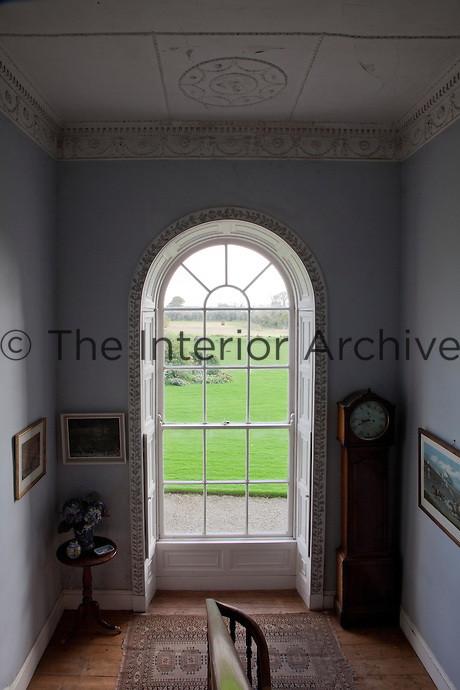 The long window on the staircase landing looks out over the lawns and the fields beyond