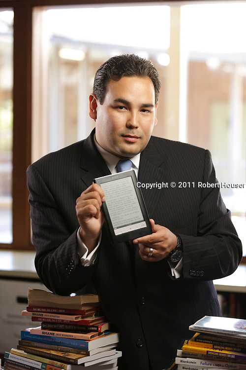 Portrait of Charles Kanavel, Director of Technology - Campbell Union High School District, holding the e-readers he has implemented in the San Jose High School District