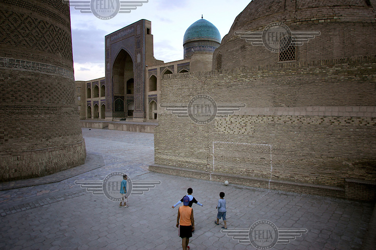 Children play football near the Mir-i Arab madrasah in the old city.