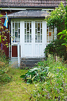 Traditional style Swedish wooden painted house. A door Overgrown unkempt garden. A veranda. Smaland region. Sweden, Europe.