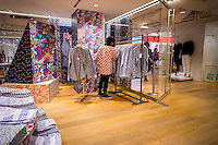 An employee arranges Liberty London merchandise in the Uniqlo store on Fifth Avenue in New York on Thursday, March 24, 2016 during the collaboration between Uniqlo and Liberty London, a company known mostly for its distinctive floral patterned fashions. (©Richard B. Levine)