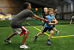 SIOUX FALLS, SD - JULY 2:  Campers Donnie Stoltz, center, makes a move past Chris Bitz, left, and Jon Rames during drills at the Riggs Football Academy Tuesday night at the Sanford Fieldhouse. (Photo by Dave Eggen/Inertia)