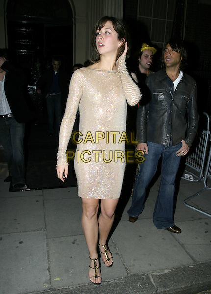 MARGOT STILLEY.MAC VIVA GLAM V - Launch Party.Home House, London W1.April 21st, 2005.full length sequins cream silver dress gold sandals touching head.www.capitalpictures.com.sales@capitalpictures.com.© Capital Pictures.