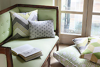 A pale green fabric has been used to re-upholster an antique sofa, while matching green and grey patterned cushions are scattered nearby