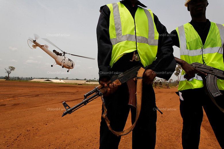 Security guards hold Kalishnkovs while a helicopter lands to pick up a shipment of gold.  Newmont Ghana is a two year old gold mine that pulls about 500,000 onces a year out of this gold mine.  They shipped out 14 bars with an average weight of 22KG each and worth about 7 million USD.