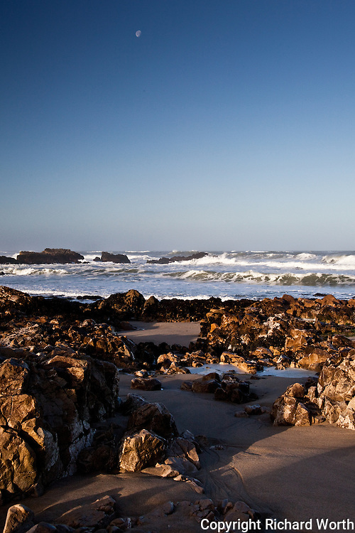 The rugged beach at Pescadero State Beach with a speck of moon, waves and long, morning shadows.