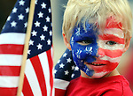 Steven  Szemreylo, 5, of Tolland, looks out at the parade participants surrounded by flags and wearing a red white and blue face, Tuesday, July 3, 2012, getting ready for the annual July 4th kids parade in Rockville, during Vernon's July 4th celebration. (Jim Michaud/Journal Inquirer)