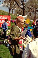 Punk activist with orange hair age 25 leafleting In the Heart of the Beast May Day Festival.  Minneapolis Minnesota USA