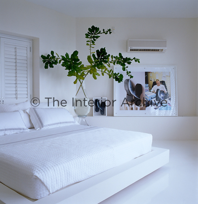 The master bedroom has an all white colour scheme, a platform bed and artwork by Horacio Cassinelli