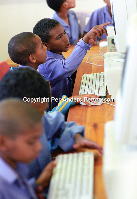 CAPE TOWN, SOUTH AFRICA - MAY 7: Students at Nooitgedacht middle school work on computers with the free Linux operating system on May 7, 2004 in Cape Town, South Africa.  The school, located in a poor area of Cape Town has an impressive computer lab, and the free system has made a big difference in the school. Many schools, companies, and governments around the world has started to use the Linux system, a tough competitor to the more expensive Microsoft Windows based system. Linus Thorwalds, a Finnish computer scientist in 1991, invented Linux and he released the Linux's source code. It started a software movement that has since produced a range software programs.   .(Photo: Per-Anders Pettersson/Getty Images)......