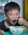 Eight-year old Lance Macapanas enjoys a meal in the United Methodist Church in the Parola neighborhood of Tondo, a poor section of Maniila, Philippines. Nursing students from the Mary Johnston College of Nursing regularly visit the neighborhood to do health education and monitor the health of residents, at the same time running  a feeding program for neighborhood children.<br /> <br /> The nursing school is supported by United Methodist Women.