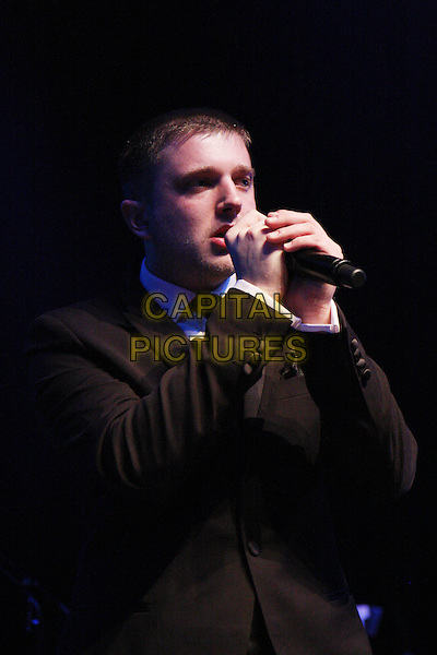 PLAN B (Ben Drew).Plays live in concert at Shepherd's Bush Empire, London, England, UK, .April 16th 2010..music gig on stage performing .half length microphone black tie suit hands singing .CAP/MAR.© Martin Harris/Capital Pictures.