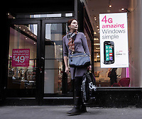 A woman walks next to a banner of the new Nokia Windows Smartphone Lumia 710 in a T-Mobile store in New York, United States. 11/01/12.  Photo by Kena Betancur / VIEWpress.