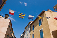 Colorful flags fly between buildings, Saint Tropez, France