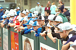 Little Leaguers line up along the fence  before introductions on opening day of Little League
