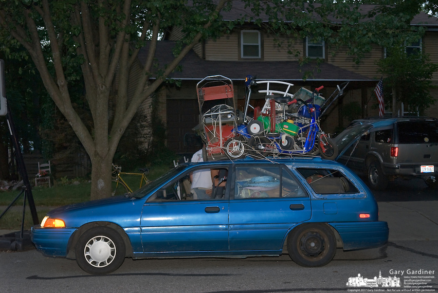 A family car is stacked high with items collected from garbage piles set by the roadside in a residential neighborhood. The car is one of several vehicles, mostly pickup trucks, that travel the neighborhoods the night before garbage pickup retrieving items they think may have value.