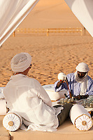 A man pours tea for a woman in the tented sitting area at the centre of the desert camp