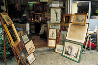 Clignancourt Flea Market shop with paintings and art prints on easels outside, in widows and on walls inside. Owner sits at desk in rear beside pile of exhibit-format books. Prints in vertical bin. Paris, France.