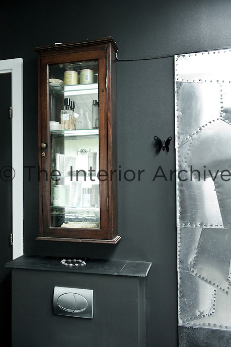 An antique cabinet contrasts with the contemporary aesthetic of the rest of the bathroom