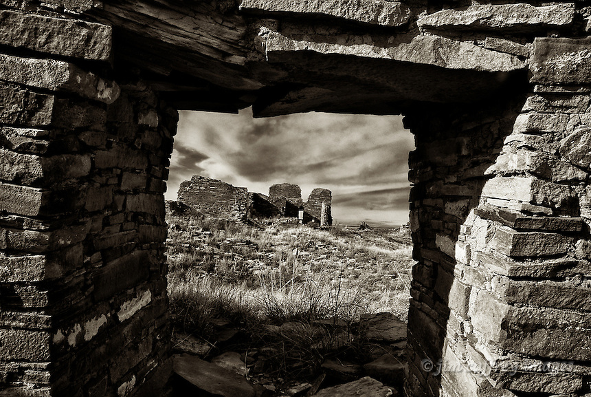 A sepia toned image of the Great House at Pueblo Pintado, a Chacoan outlier in the San Juan Basin of northwestern New Mexico, seen through a doorway in a nearby ruin.
