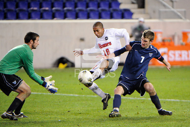 Walter Hines (19) of the St. John's Red Storm scores the game winning goal as Kyle McCarthy (7) and goalkeeper John Fogarty (1) of the Villanova Wildcats defends. St. John's defeated Villanova 2-0 during the second semifinal match of the Big East Men's Soccer Championships at Red Bull Arena in Harrison, NJ, on November 11, 2011.